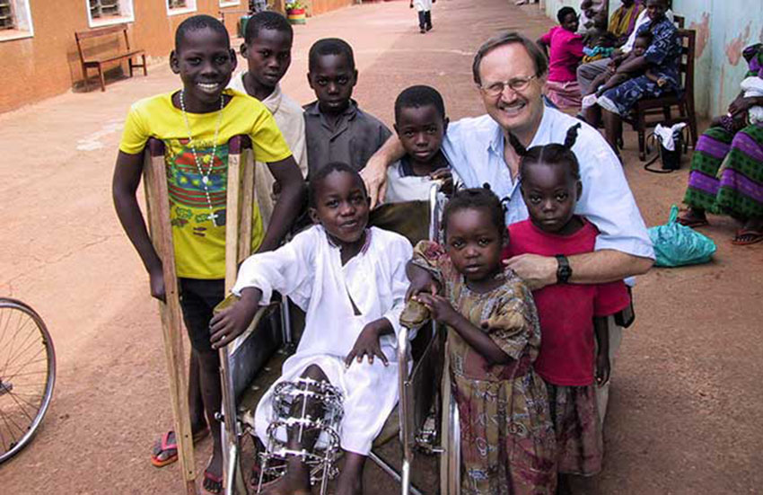 Dr. Norgrove Penny with children in Uganda