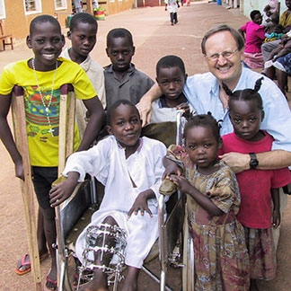 Norgrove Penny standing with children with disabilities in Uganda