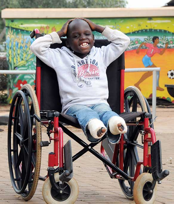 Smiling Edrine sitting in his wheelchair