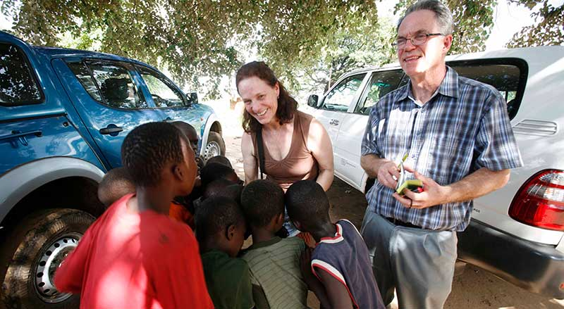 Lynn and Alan greeting kids in Africa