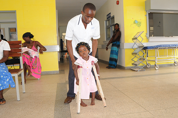 Benita standing on crutches with the assistance of a doctor