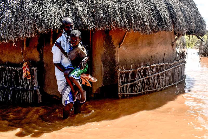 A man holding his son in floodwaters after the Tana River overflowed. Photo credit: AFP/Andrew Kasuku