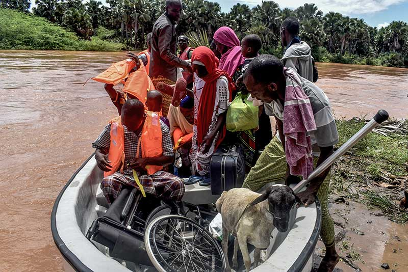 Villagers of Onkolde and a goat being evacuated by a Kenya's Red Cross boat from their flooded village after the Tana River overflowed. Photo credit: AFP/Andrew Kasuku