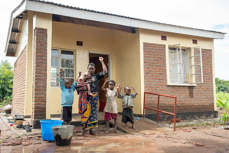 Zione and her kids in front of her new home
