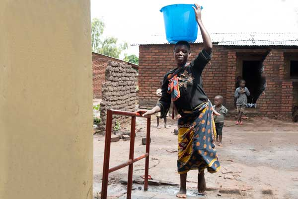 Zione walking to her new home with a bucket of water on her head.