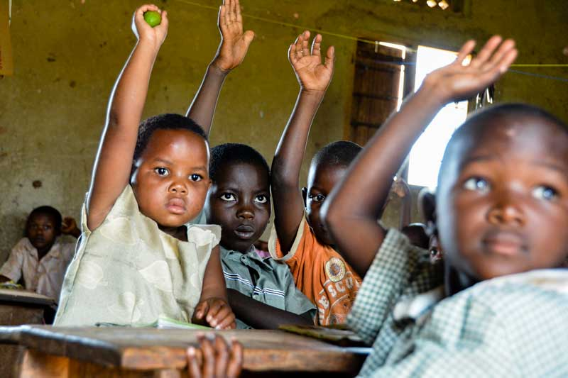 Kids in classroom with their hands up